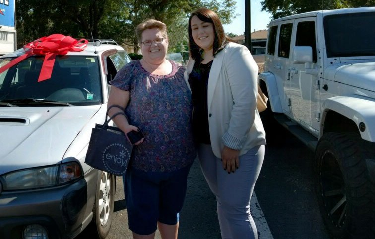 Two women stand in front of a car smiling