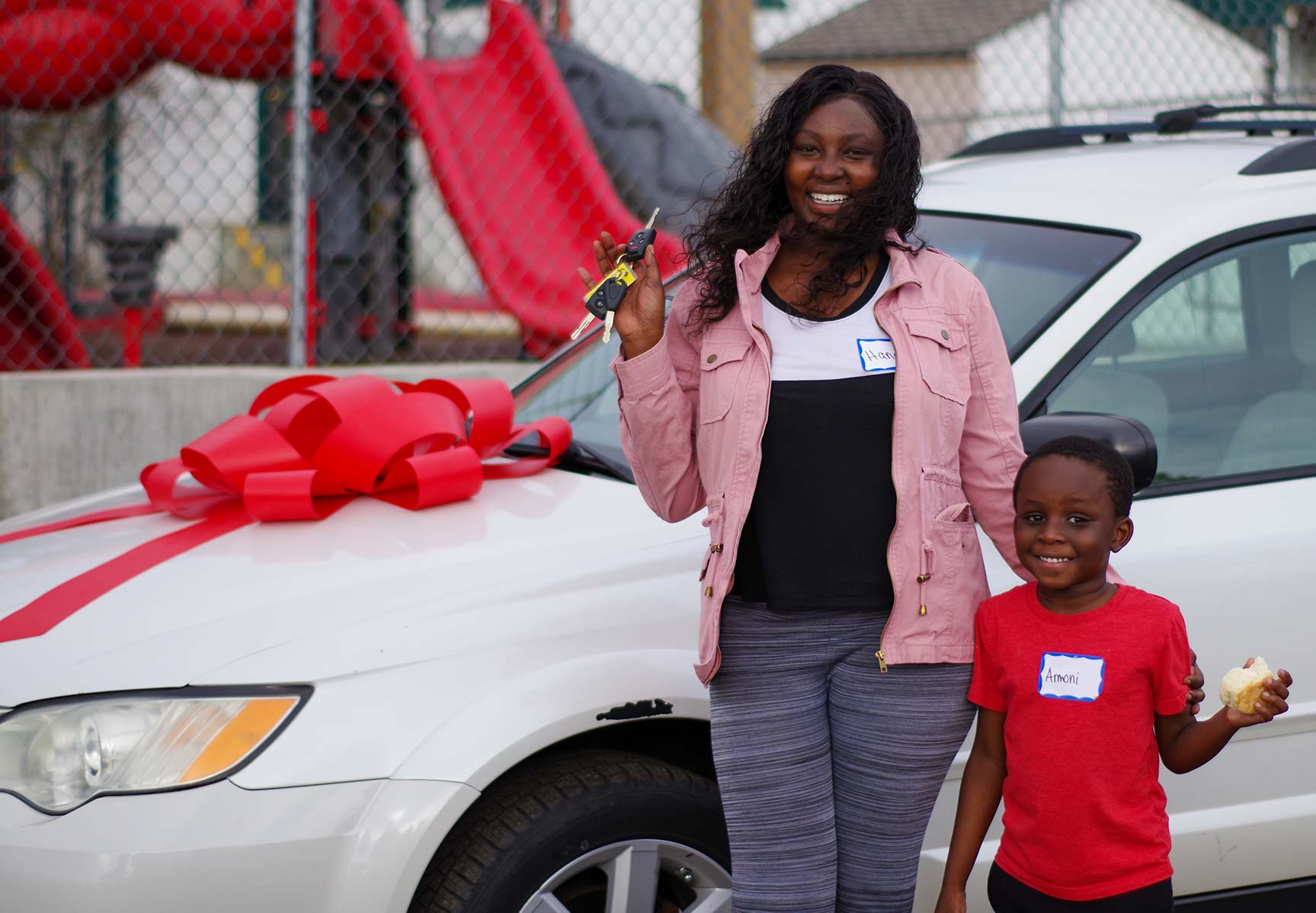 A woman and her son stand in front of a car smiling
