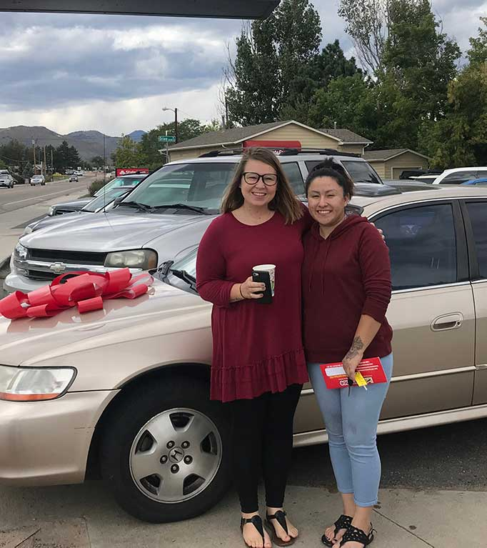 Two young women are standing in front of a car with a giant bow on the hood, they are smiling