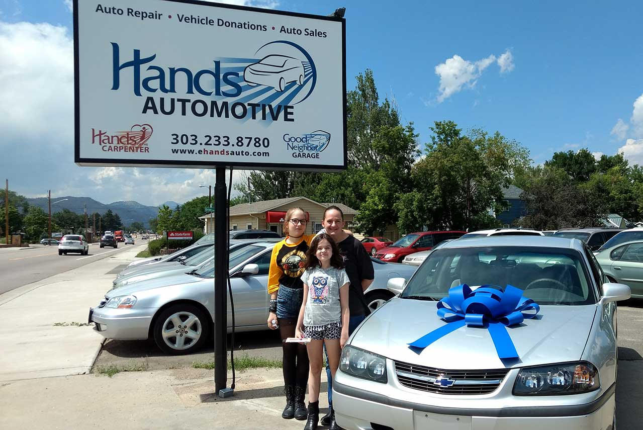 A mother and her two school aged daughters stand in front of a car with a giant bow on the hood