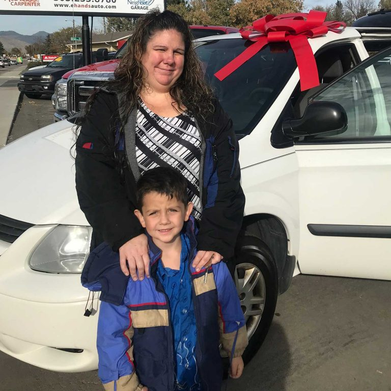 A woman and her young son stand in front of a car and smiling, the car has a giant bow on the hood