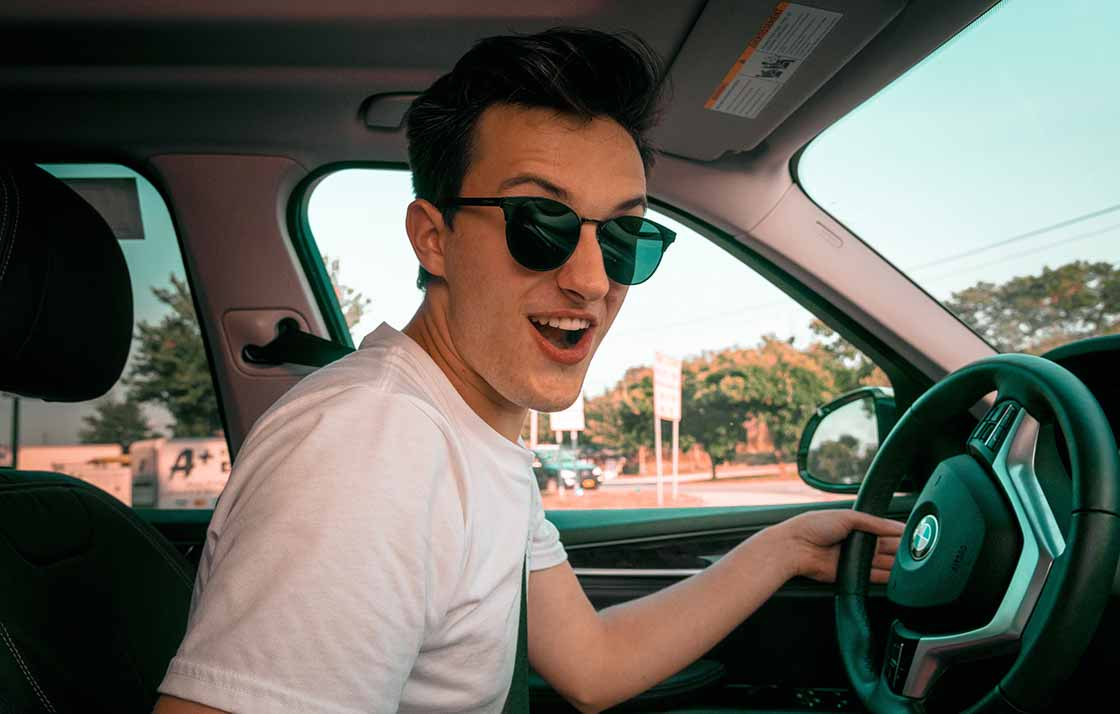 A young man is driving a car