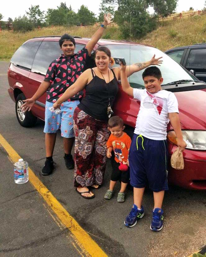 A mother with her three sons stands in front of a minivan, they are celebrating