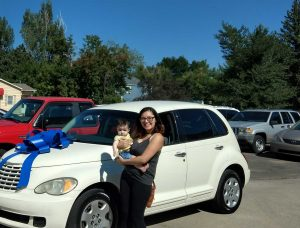 A woman holding a small child stands in front of a car and smiling, the car has a giant bow on the hood
