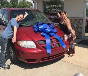 Two women stand in front of a red van smiling, there is a giant bow on the hood of the car