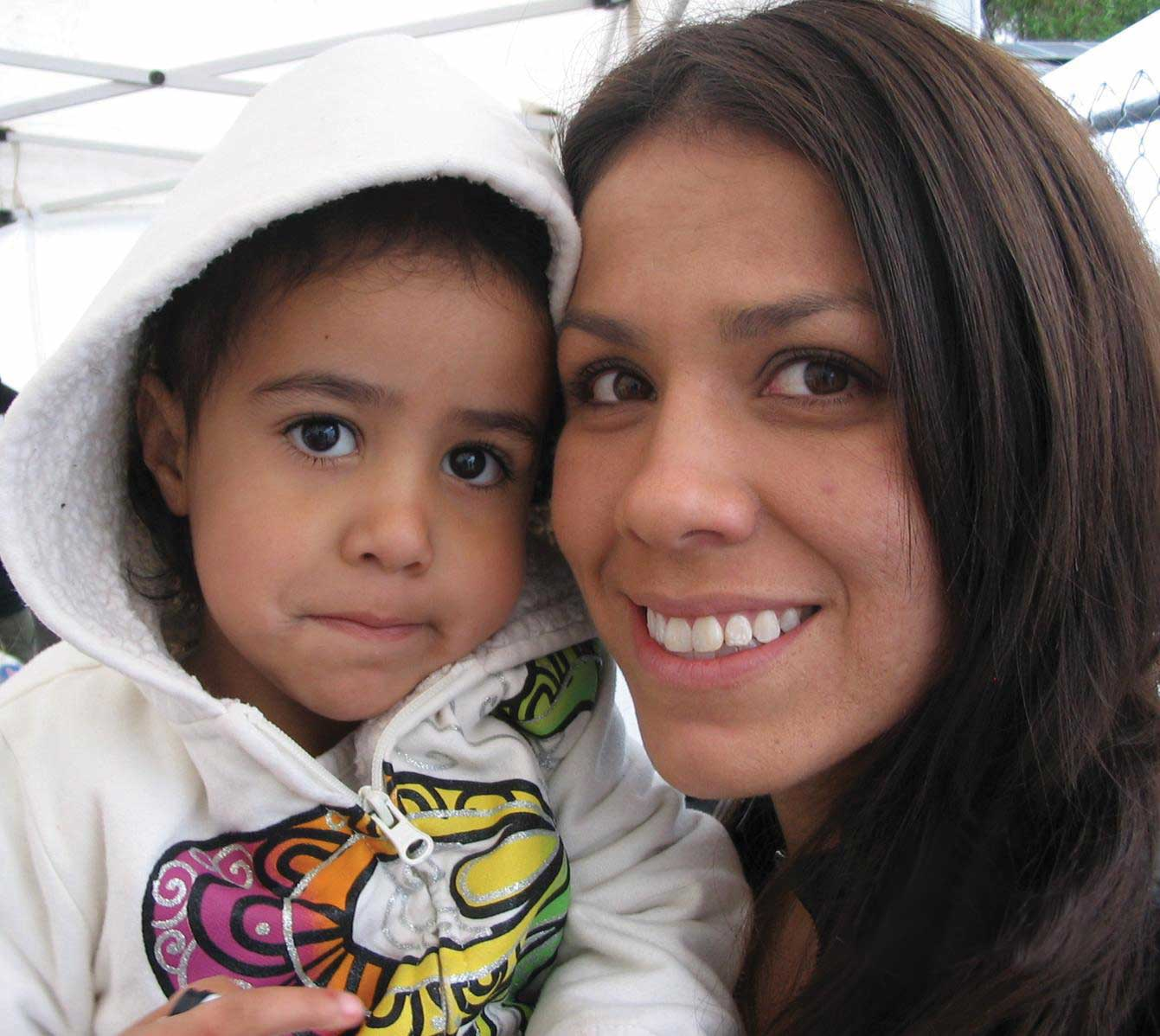 A young woman holds her small child, they are smiling