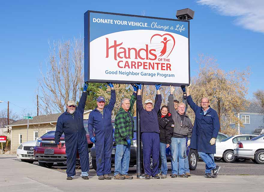 A group of eight volunteers pose in the parking lot of a local charity