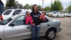 A young woman holding her small children is standing in front of a car and smiling, the car has a giant bow on the hood