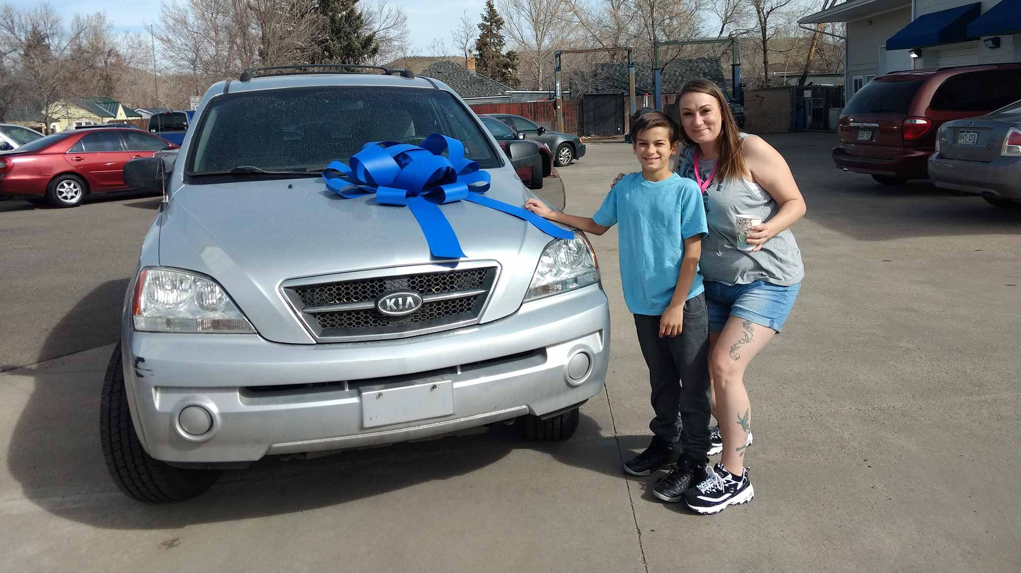 A woman and her son stand in front of a car with a giant bow on the hood, they are smiling
