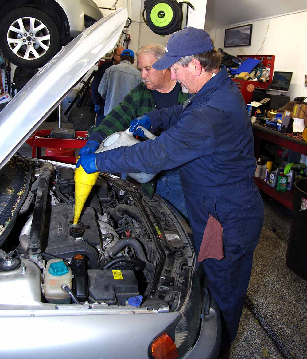 Two mechanics work on the engine of a car in the garage