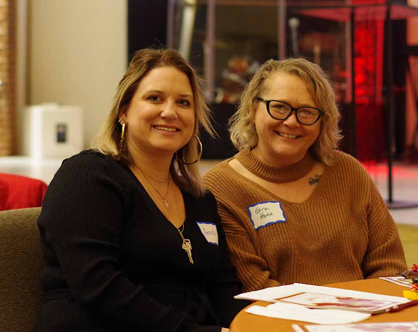 Two women sit at a table at an event
