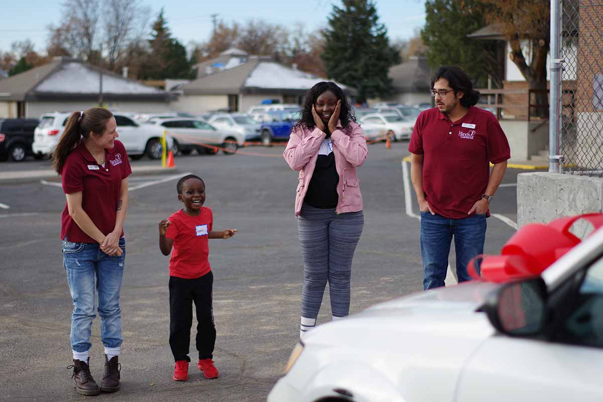 A mother and son are surprised and excited looking at a car given to them